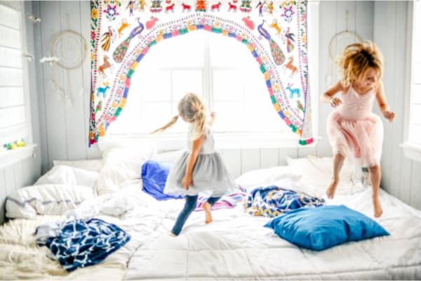 niñas saltando sobre la cama